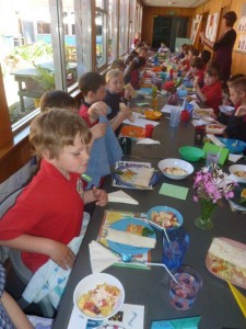 A long table of healthy students enjoying lunch